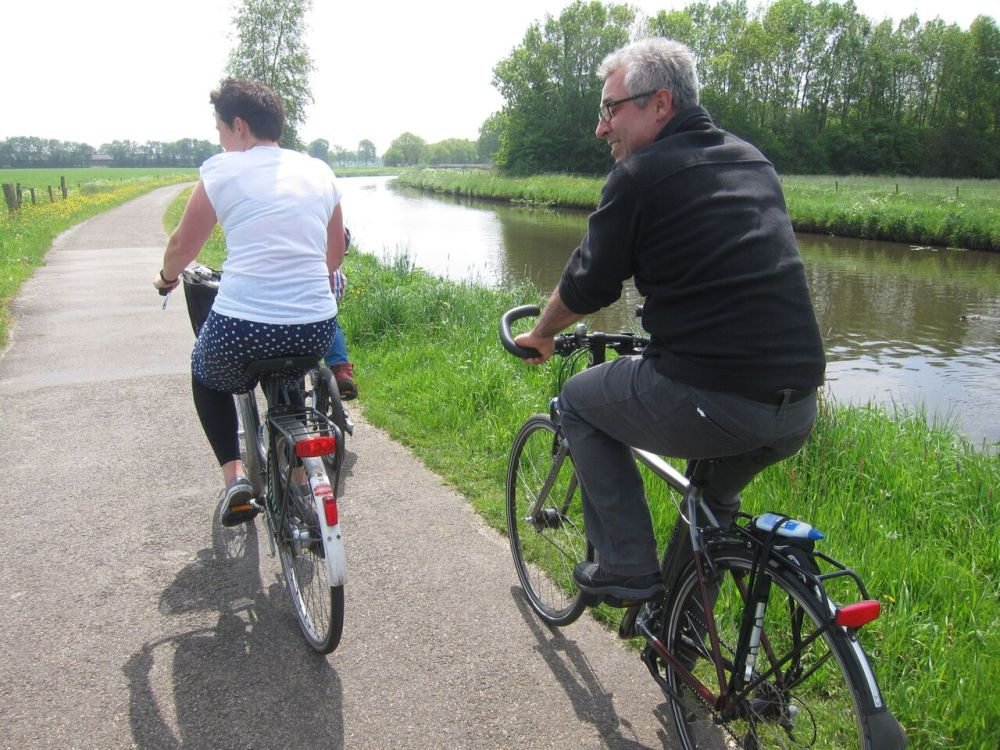 Mariele and Chris on bicycles by a canal