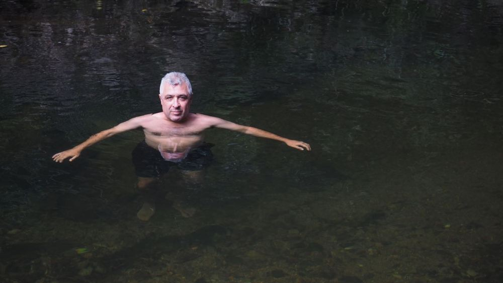 Jordo in dark creek water with his face doubled in reflection