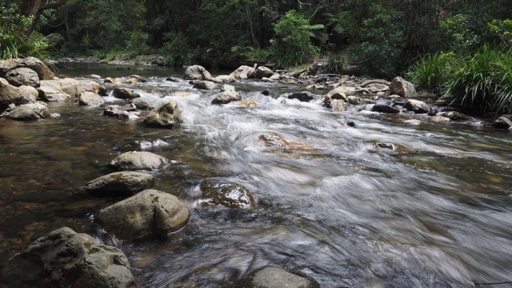 Creek water flowing fast over rocks