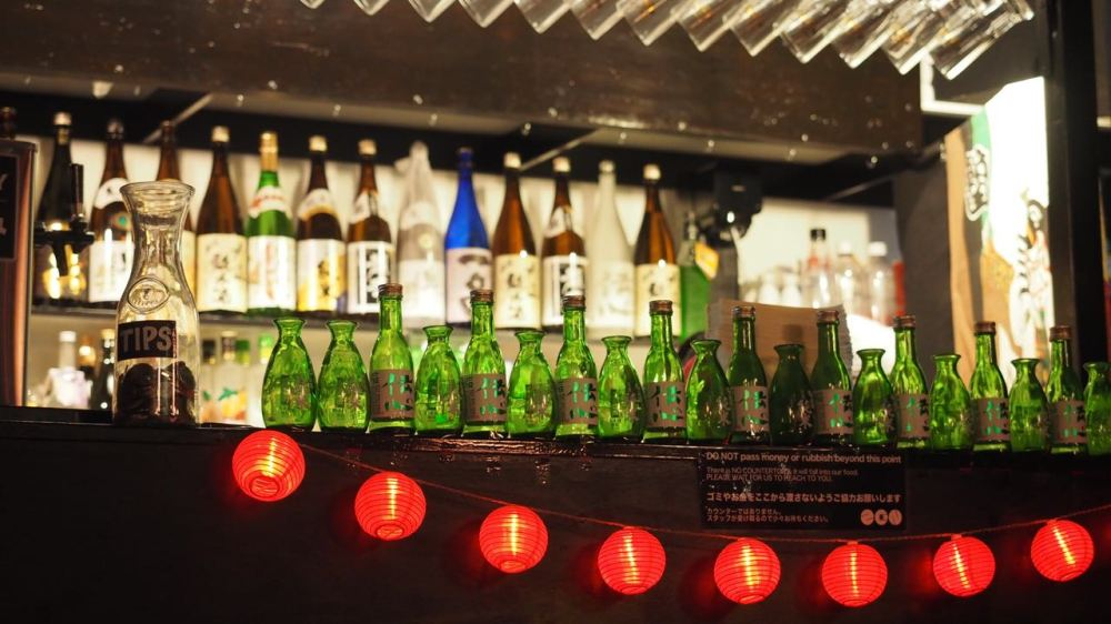 Bottles lined up along bar with red lanterns